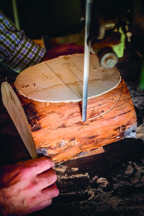 Erst wird die Bandsäge benutzt, um dem Zirbenholzrohling die Form zu geben, hinter der sich später ein Gesicht verstecken wird.